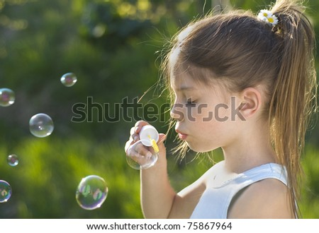 Little girl blowing soap bubbles - stock photo