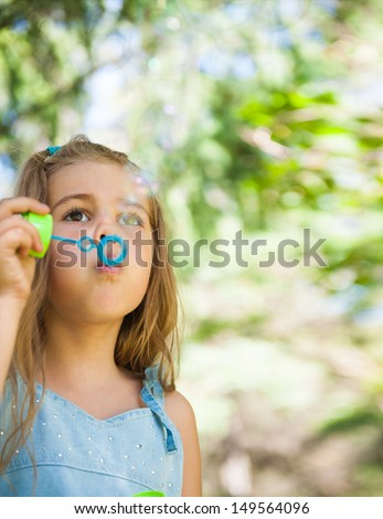 Little girl blowing soap bubbles outdoors at park - stock photo