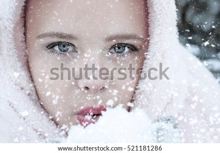 Little girl blows snow on a snowflakes bokeh