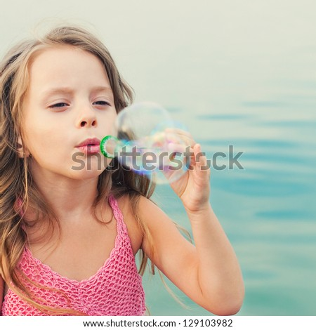 Little girl blows soap bubbles outdoor. Happy child - stock photo