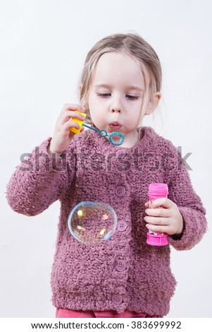 little girl blows soap bubbles over white background - stock photo
