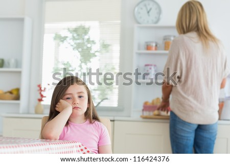 Little girl bored in the kitchen with mother working at counter - stock photo