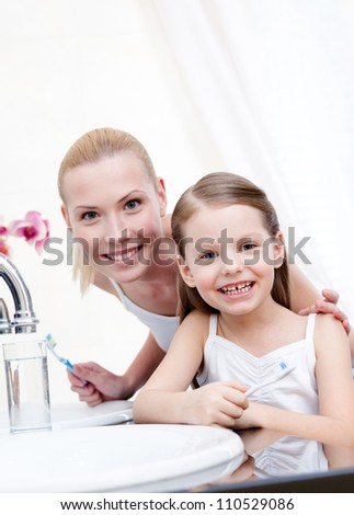 Little girl brushes her teeth with her mum - stock photo