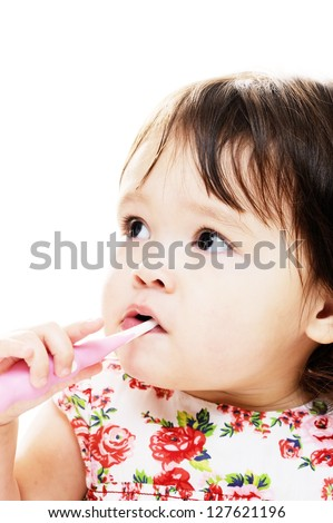 Little girl brushing her teeth with pink toothbrush