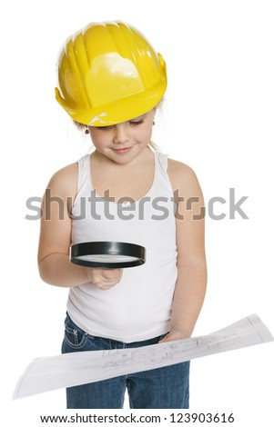 Little girl builder in yellow helmet analyzing drawing through the magnifying glass, over white background - stock photo