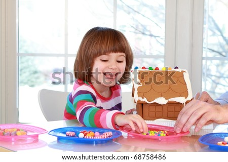 Little girl building and decorating gingerbread house for Christmas - stock photo
