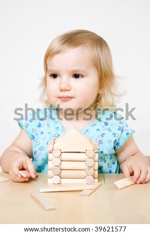 Little girl building toy house