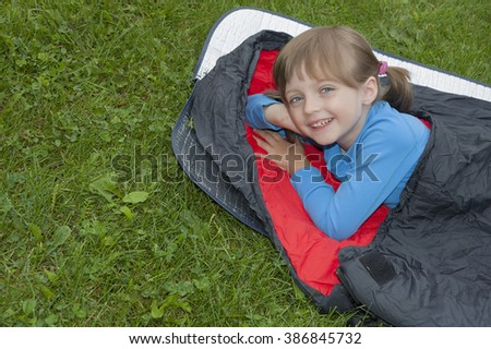 little girl camping with sleeping bag - stock photo