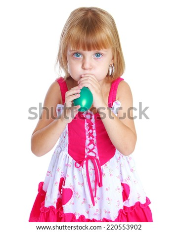 Little girl carefully inflates the balloon, isolated on white background.The concept of development of the child, the child's upbringing. - stock photo