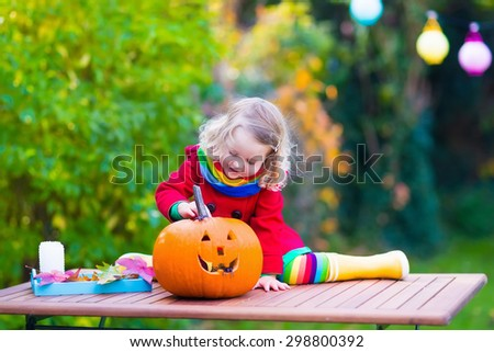 Little girl carving pumpkin at Halloween. Dressed up child trick or treating. Kids trick or treat. Child in witch costume playing in autumn park. Toddler kid with jack-o-lantern.  - stock photo