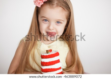 Little girl celebrating a birthday with a small red velvet cake. Cute blond preschooler holding beautiful tasty cake with strawberry