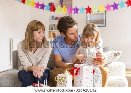 Little girl celebrating birthday party in modern white house - stock photo