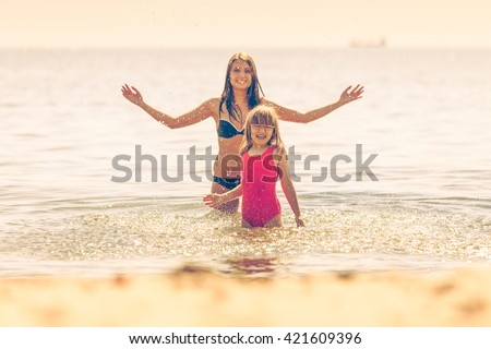 Little girl child and mother having fun in ocean. Kid and woman bathing in sea splashing water. Summer vacation holiday relax. Instagram filter. - stock photo