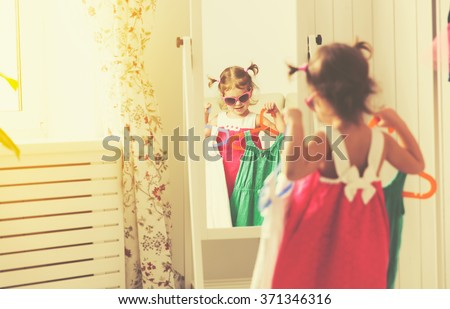 little girl child looks into the mirror and choose dresses - stock photo