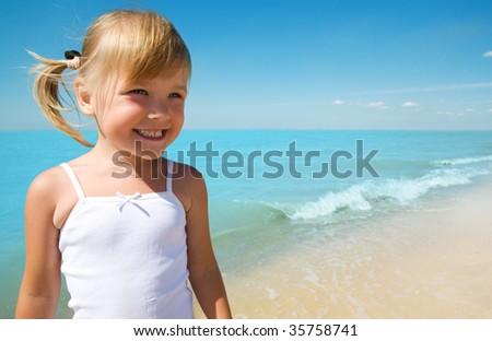 little girl child on coast of sea - stock photo