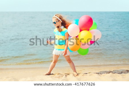 Little girl child playing on beach with colorful balloons near sea  - stock photo
