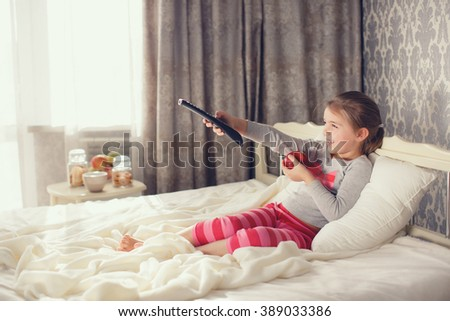 Little girl child remote control watching tv set lying on bed in room. 6 years old child watching tv laying down on a white carpet at home alone. cute little girl - stock photo
