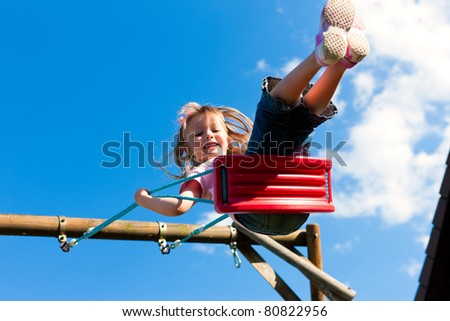 Little girl child sitting on a swing in the garden playground; she has lots of fun - stock photo