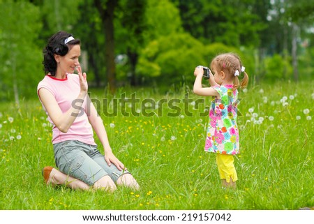 little girl child to learn to photograph with his mother in the meadow. little baby pictures with mom