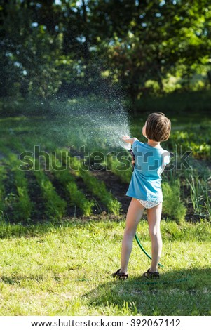 Little girl child watering vegetables in small garden.