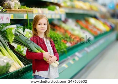 Little girl choosing a leek in a food store - stock photo