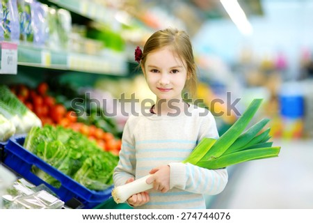 Little girl choosing a leek in a food store or supermarket - stock photo