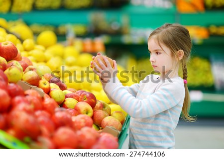 Little girl choosing an apple in a food store or a supermarket - stock photo