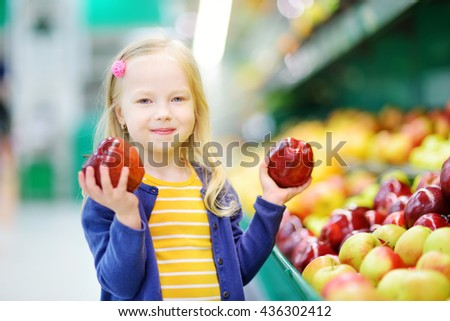 Little girl choosing ripe apples in a food store or a supermarket