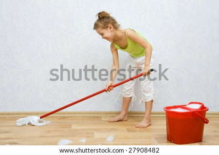 Little girl cleaning the floor in the room - stock photo
