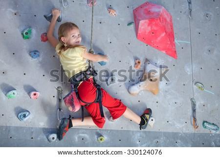 little girl climbing a rock wall indoor - stock photo