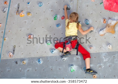 little girl climbing a rock wall indoor - stock photo