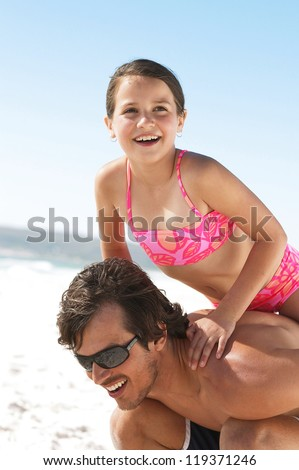 Little girl climbing up on dads shoulders for a tall ride during a fun day at the ocean - stock photo