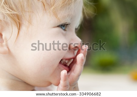 Little girl closing her mouth by hand while laughing. Close-up portrait of a pretty blond european child.  Perfect facial features of an amazing toddler. Expressing emotions. Colorful photo. - stock photo