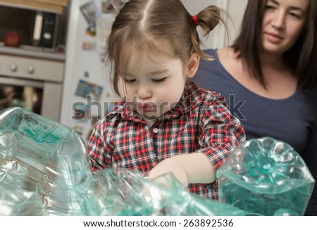 Little girl collecting plastic for recycling with her mother  - stock photo