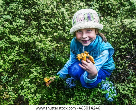 Little girl collects mushrooms.