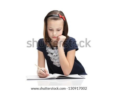 Little girl concentrates on the home task, isolated, white background - stock photo