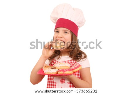 little girl cook eating sweet donuts - stock photo