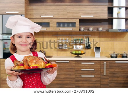 little girl cook with chicken in kitchen - stock photo