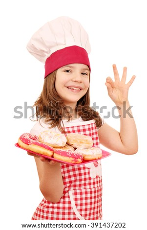 little girl cook with sweet donuts and ok hand sign