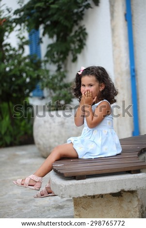 Little girl covering her mouth with her hands. Emotions of the child. - stock photo