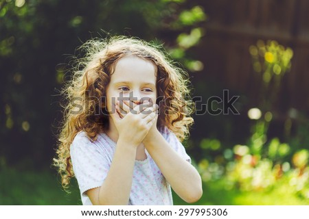 Little girl covering her mouth with her hands. Surprised or scared.  - stock photo