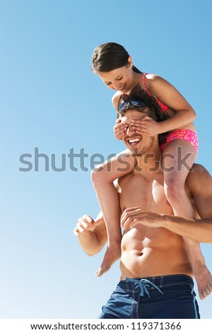 Little girl covers her dads eyes as she is carried on his shoulders while playing at the beach - stock photo