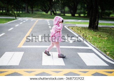 Little girl crossing the road on the crosswalk in the park - stock photo
