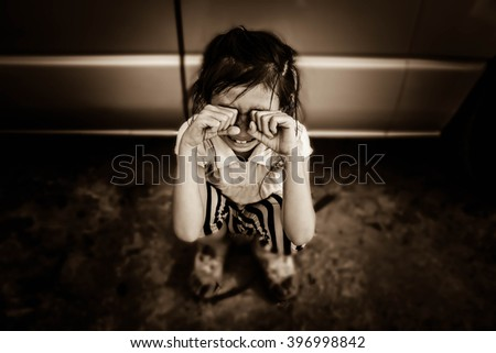 Little girl crying near car,Blurred sepia vintage tone,Emotion - stock photo