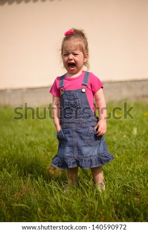 Little girl crying outdoors - stock photo