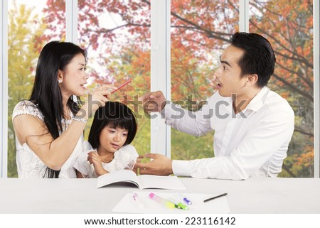Little girl crying while studying with her parents quarreling at home - stock photo