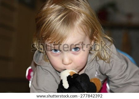 Little girl cuddling with her Soft toy dog - stock photo