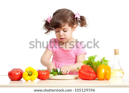 Little girl cutting vegetable for salad. Concept of healthy food. - stock photo