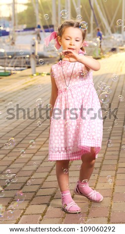 Little girl dancing with bubbles