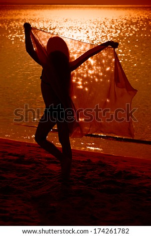 Little girl dancing with veil on the beach at sunset - carefree and happy - stock photo